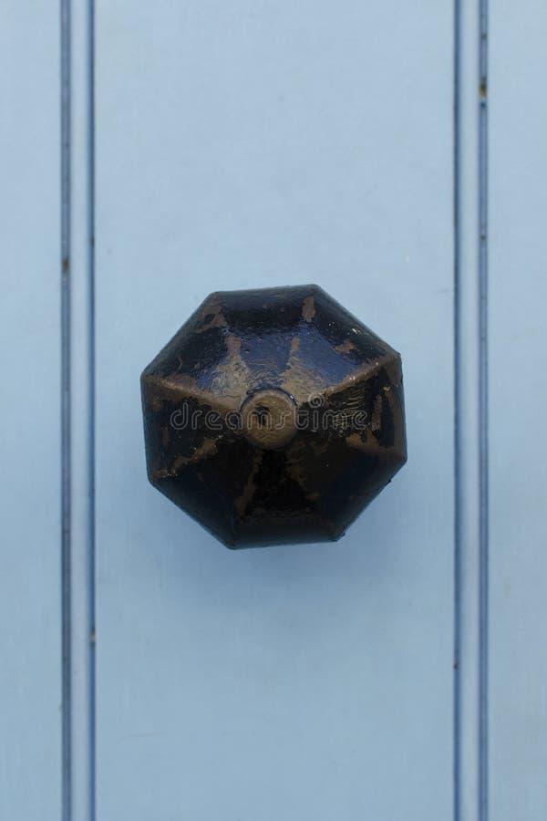 有破旧的黑油漆的葡萄酒铜门把手在浅兰的woode 免版税库存图片