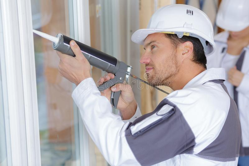 有硅树脂的安装工在建造场所 库存图片