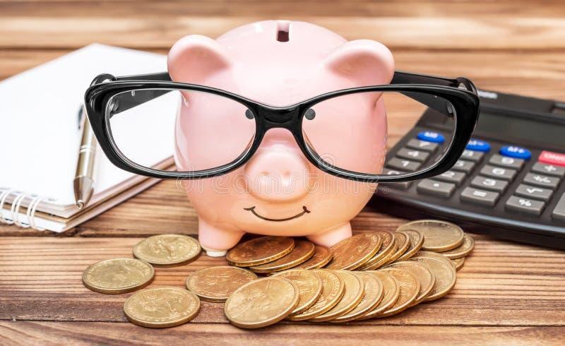有硬币、计算器、笔记薄和玻璃的存钱罐在工作场所 免版税库存图片