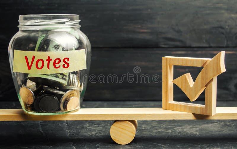 有硬币和词'表决的玻璃瓶子和在等级的一个复选框 投票的概念支持金钱 贿赂选民 腐败i 免版税库存图片