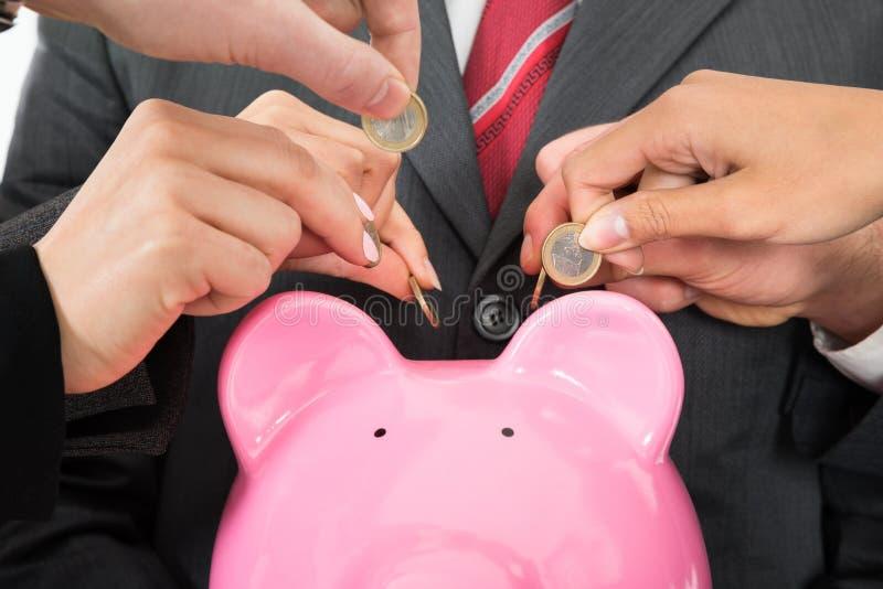 有硬币和piggybank的买卖人手 免版税库存照片