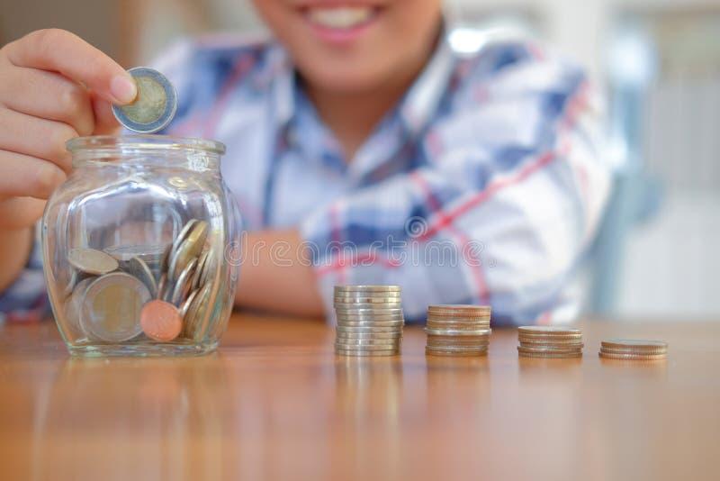 有硬币堆瓶子的亚裔孩子男孩儿童孩子 金钱储款 免版税库存照片