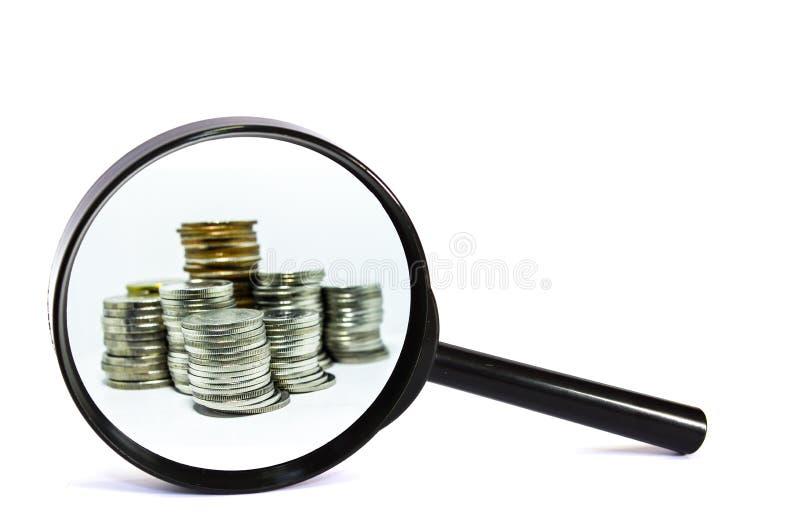 有硬币特写镜头的放大镜在白色背景 免版税库存图片