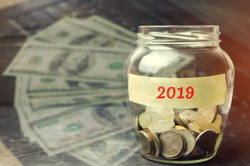 有硬币玻璃瓶子和题字的'2019年' 财政预算计划 投资和计划新年 银行票据贪心放置的节省额 库存图片