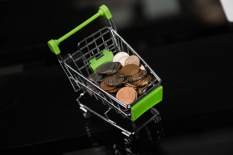 有硬币的假的手推车在黑办公桌上 免版税库存图片