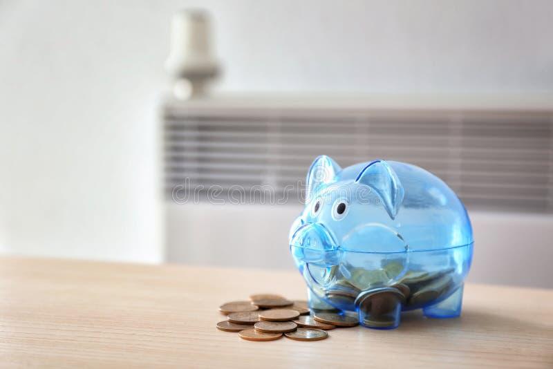 有硬币的存钱罐在calorifer附近在家 加热的保存的概念 库存照片