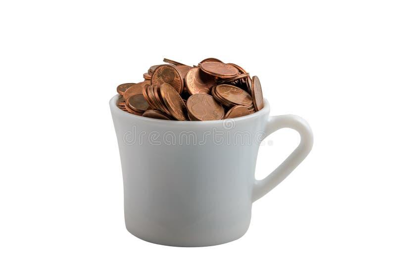 有硬币的杯在白色背景的技巧的 库存照片