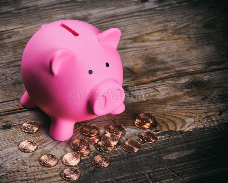 有硬币的桃红色猪钱箱 免版税库存照片