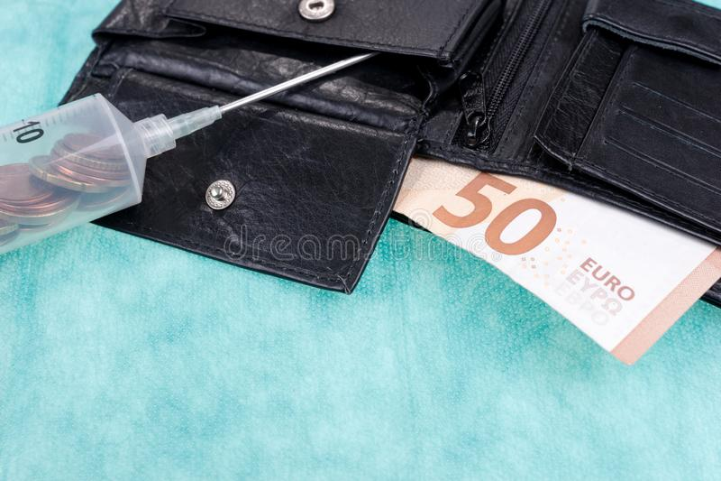 有硬币的注射器和五十欧元票据在皮革钱包里 库存图片