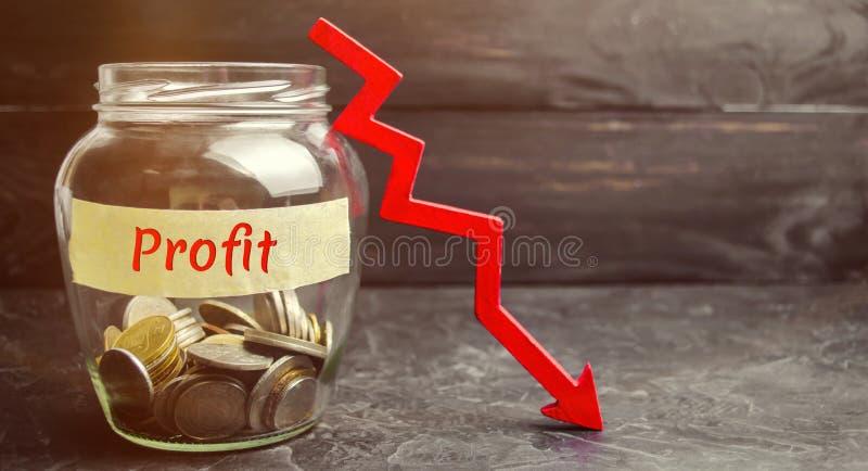 有硬币的玻璃瓶子,在箭头和词赢利下 不成功的事务和贫穷 赢利衰落 投资损失  低工资 图库摄影