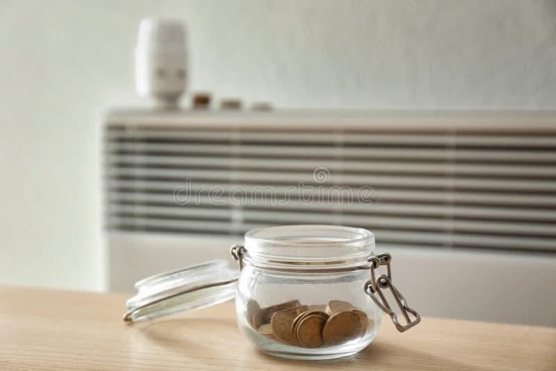 有硬币的瓶子在calorifer附近在家 加热的保存的概念 免版税库存照片