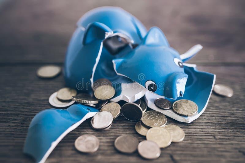 有硬币的被打碎的打破的存钱罐在土气木桌上 库存图片