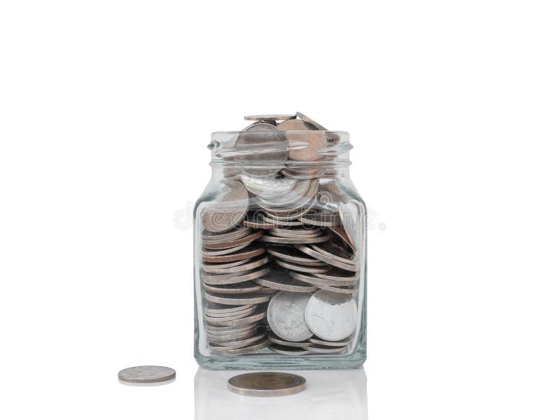 有硬币的玻璃瓶子在白色隔绝的反射性表面上 免版税库存照片