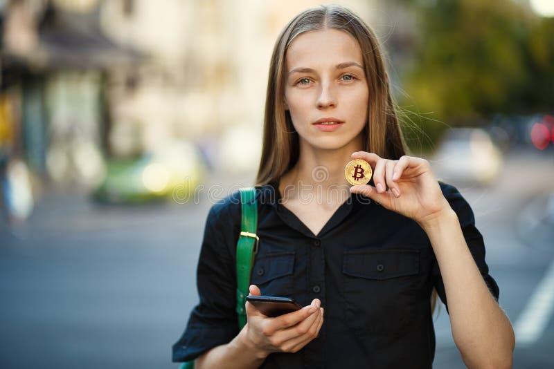 有硬币bitcoin的少妇和智能手机在手中在后面 库存图片