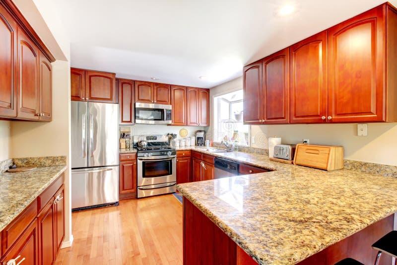 有硬木地板的,被弄脏的内阁厨房,不锈窃取冰箱和大理石柜台 图库摄影