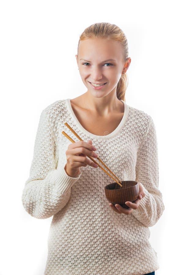 有碗和筷子的一个年轻愉快的女孩 库存照片