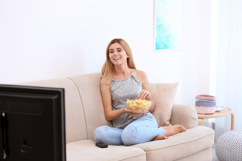 有碗的妇女在沙发的薯片看着电视 免版税库存图片