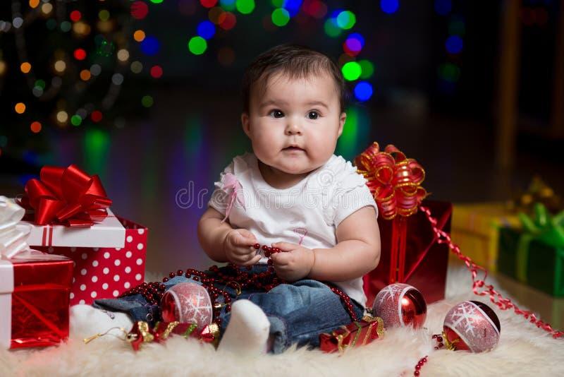 有礼品的女婴在圣诞树下 图库摄影