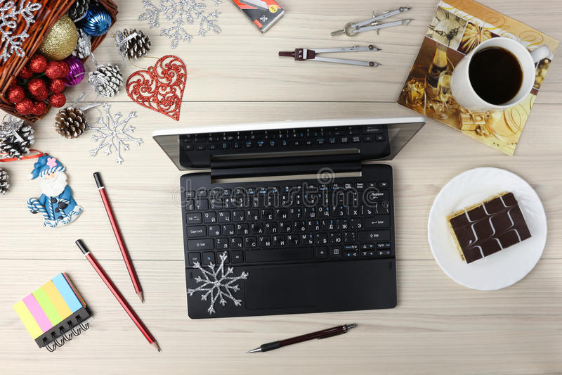 有礼物和咖啡的膝上型计算机在桌深蓝蓝色背景 企业假日概念 办公室工作场所杯  免版税库存图片