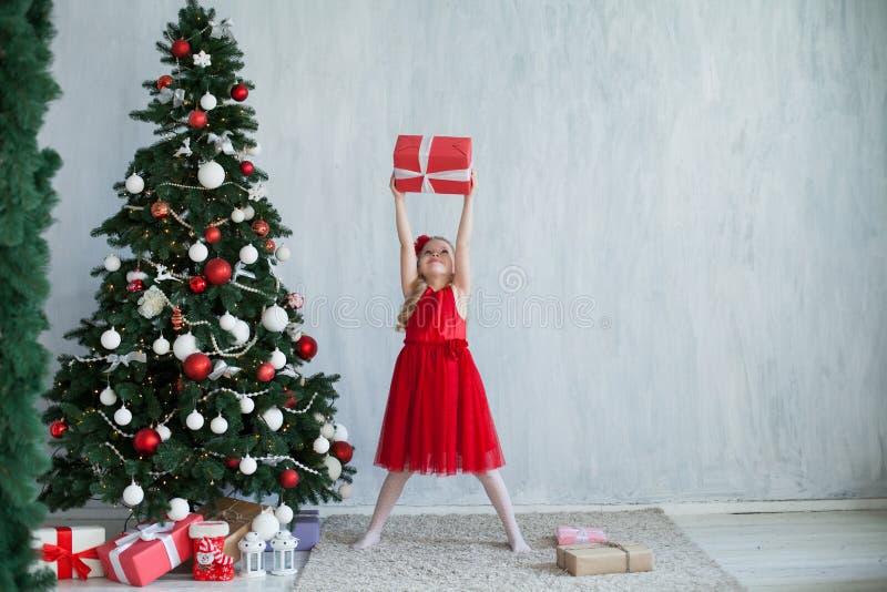 有礼物新年圣诞树的女孩在灰色背景礼物 库存图片