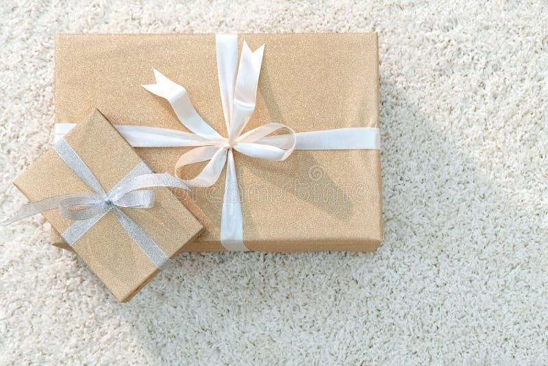 有礼物的两个箱子包裹与金黄纸和栓与白色丝带 软的白色地毯 轻的端 复制空间 免版税库存图片