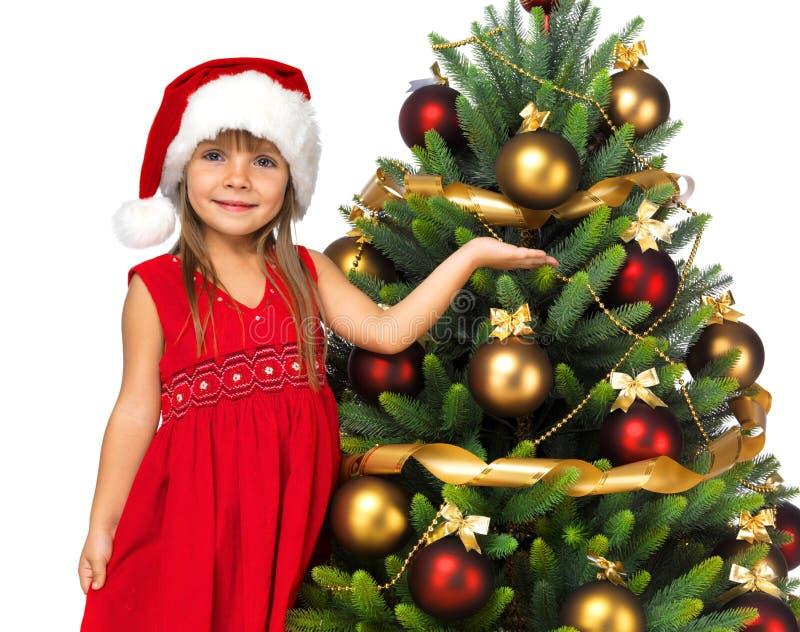 有礼物的俏丽的女孩在圣诞树附近 库存照片