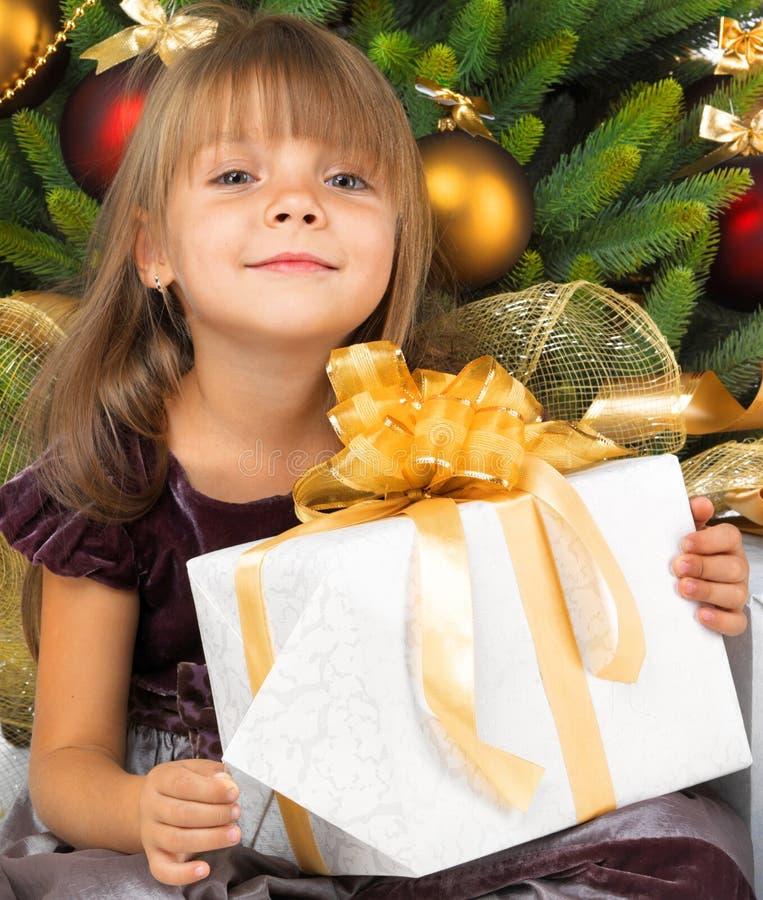 有礼物的俏丽的女孩在Cristmas树附近 免版税库存图片