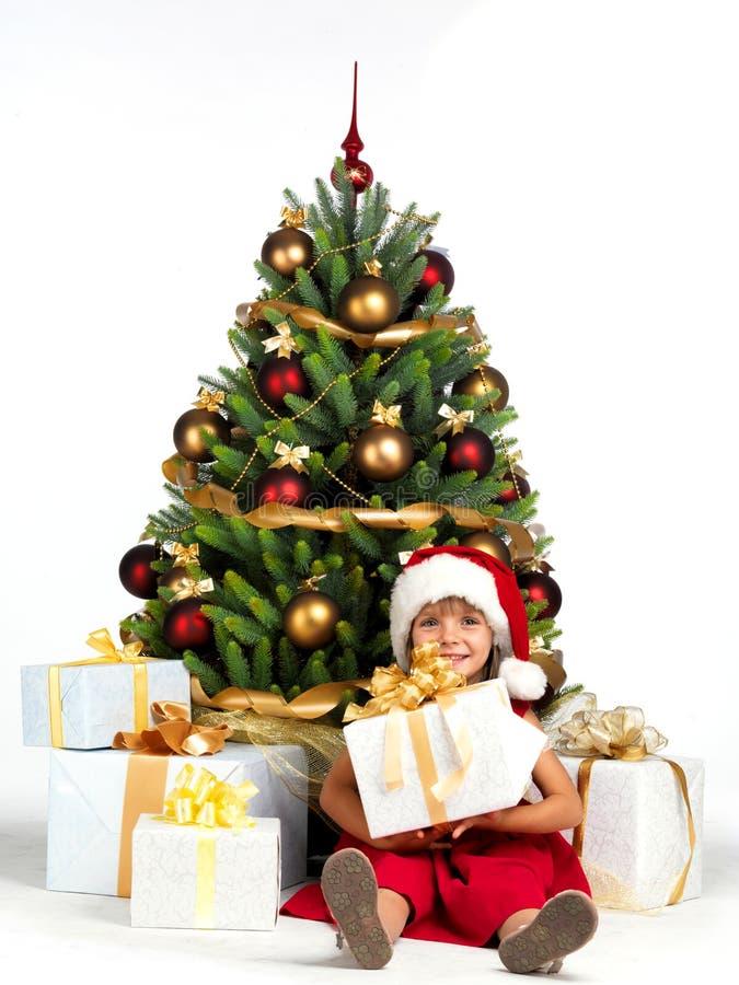 有礼物的俏丽的女孩在Cristmas树附近 图库摄影