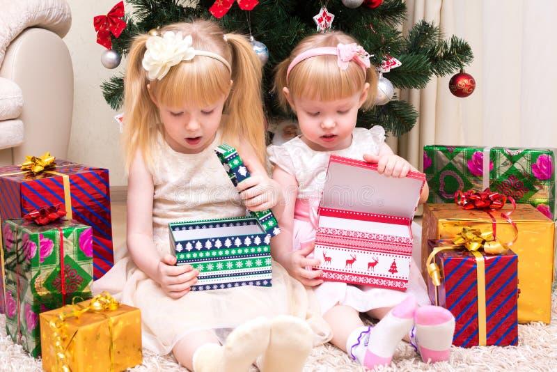 有礼物的孩子临近圣诞树 免版税库存图片