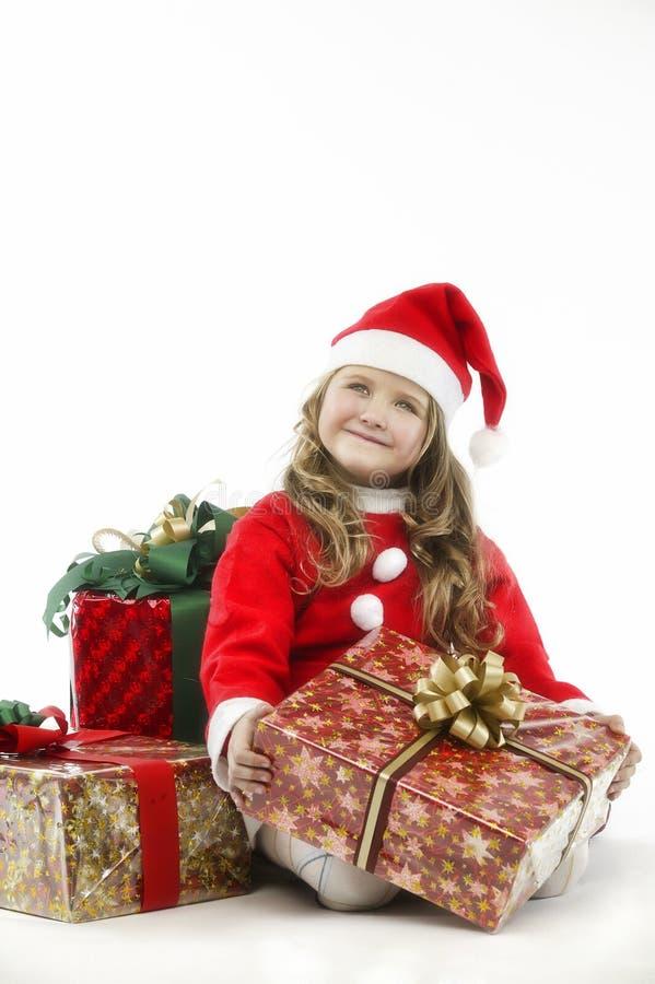 有礼物的小女孩红色礼服圣诞老人帽子在白色背景 图库摄影