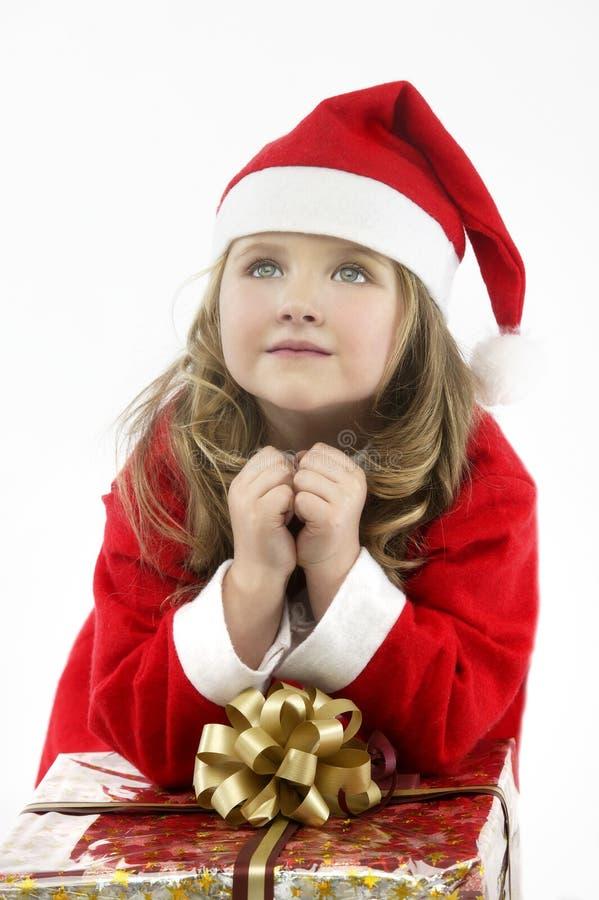 有礼物的小女孩红色礼服圣诞老人帽子在白色背景 免版税库存图片