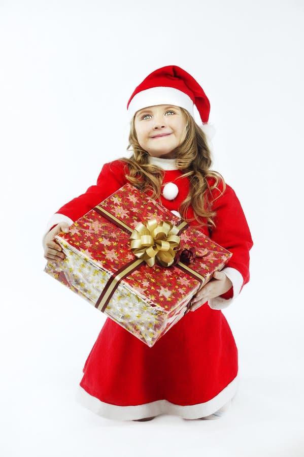 有礼物的小女孩红色礼服圣诞老人帽子在白色背景 免版税库存照片