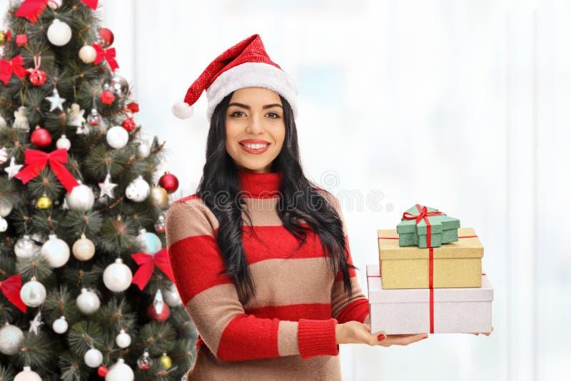 有礼物的少妇在圣诞树前面 库存图片