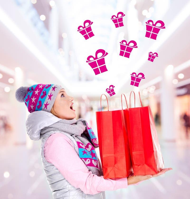 有礼物的惊奇的妇女在购物对新年以后 免版税图库摄影