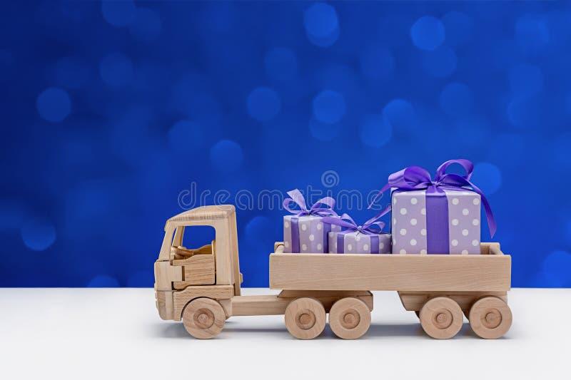 有礼物的木玩具卡车在蓝色背景的典雅的纸 圣诞节的,新年,生日,情人节惊奇 库存照片