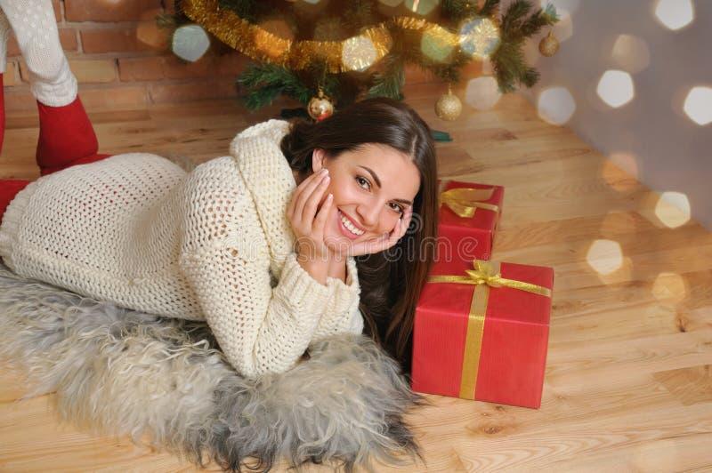 有礼物的美丽的微笑的少妇临近圣诞树 免版税库存照片