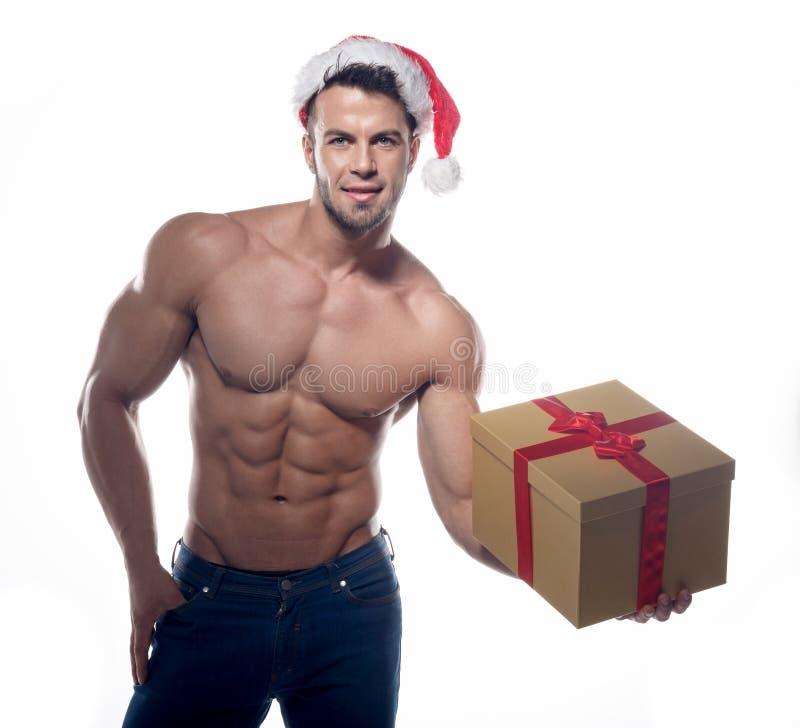 有礼物的肌肉,性感的圣诞老人 免版税图库摄影
