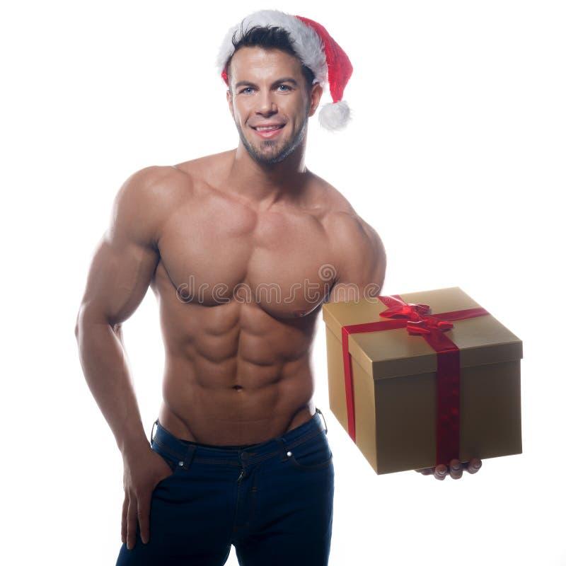 有礼物的肌肉,性感的圣诞老人 免版税库存图片