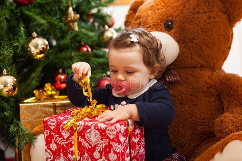 有礼物的Tddler女孩临近圣诞树 库存图片