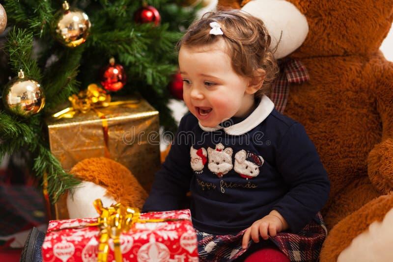 有礼物的Tddler女孩临近圣诞树 图库摄影