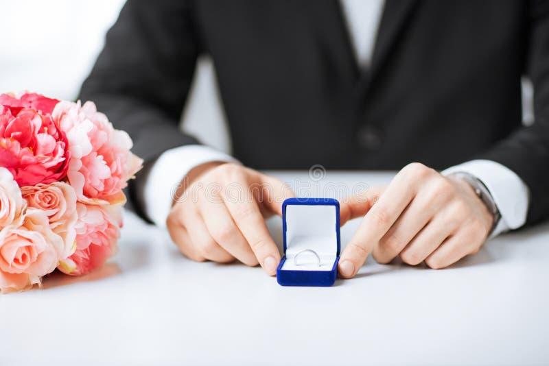 有礼物盒和婚戒的人 免版税图库摄影
