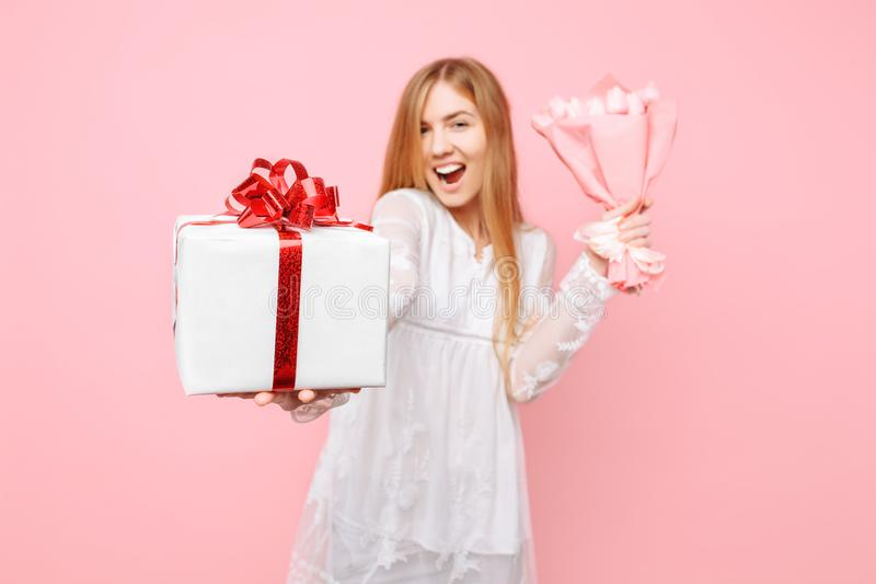 有礼物盒的一愉快的年轻女人和郁金香花束在她的手上 在桃红色背景 概念,情人节 免版税图库摄影