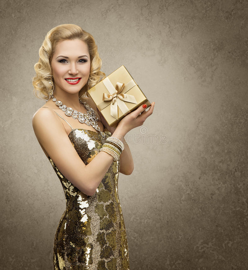 有礼物盒的富有的妇女,豪华减速火箭的女孩,光亮的金礼服 图库摄影