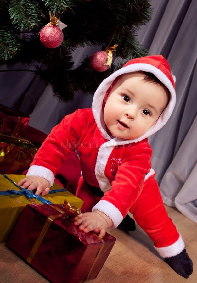 有礼物盒的小圣诞老人男孩。 免版税图库摄影