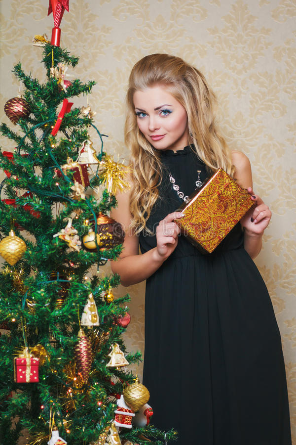 有礼物盒的少妇在新年树附近 图库摄影