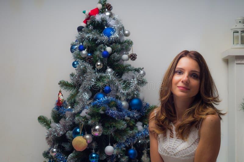 有礼物盒的年轻愉快的美女在圣诞树附近坐在房子的屋子里 库存图片