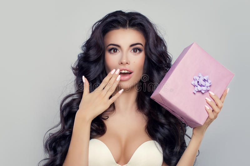 有礼物盒的惊奇的妇女 与开放嘴的美好的模型 免版税库存照片