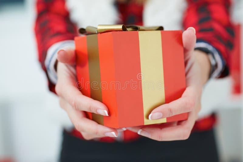 有礼物盒的愉快的妇女在手上 免版税库存图片
