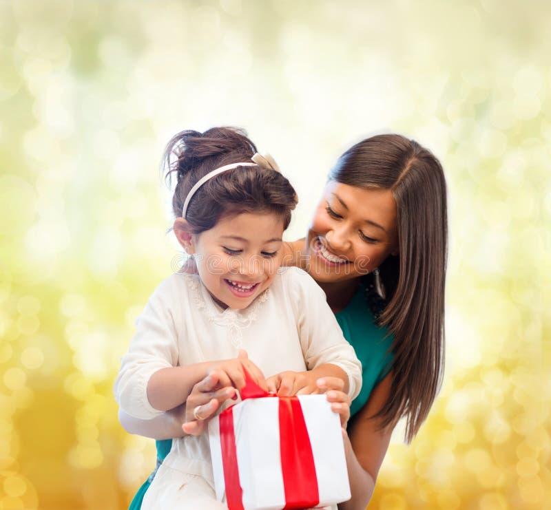 有礼物盒的愉快的母亲和儿童女孩 免版税图库摄影