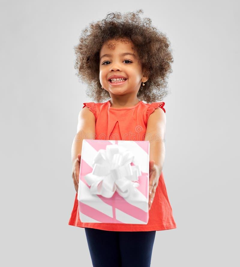 有礼物盒的愉快的矮小的非裔美国人的女孩 免版税库存图片